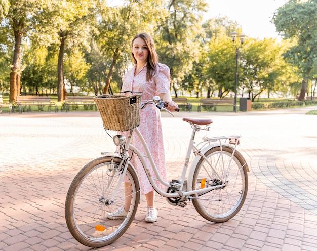 Стильная молодая женщина позирует с велосипедом