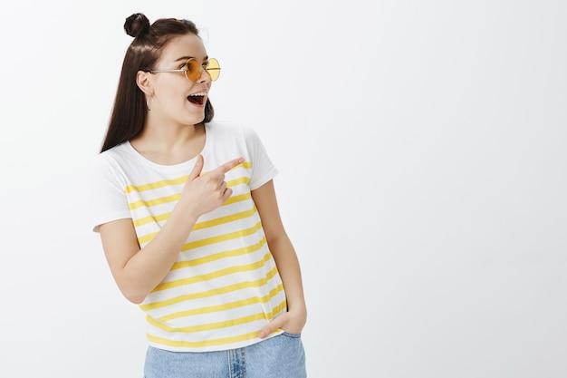 Elegante giovane donna in posa con occhiali da sole contro il muro bianco