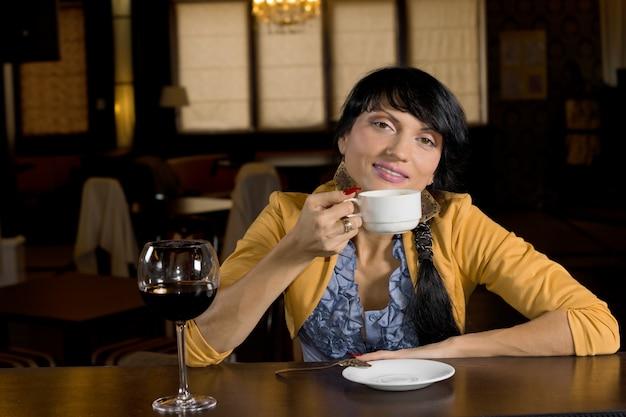 カメラに微笑むために一時停止バーでコーヒーを飲みながらリラックスしてスタイリッシュな若い女性