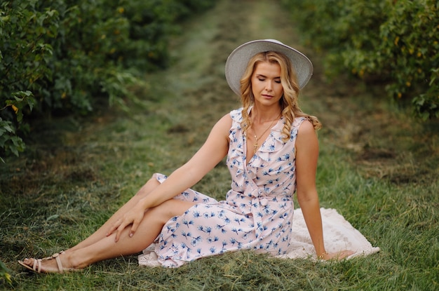 Stylish young woman in rose blue vintage dress and hat posing in green field