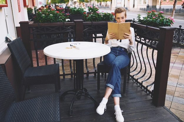Stylish young woman in a shirt with a book in her hands sits at a table in a cafe in summer