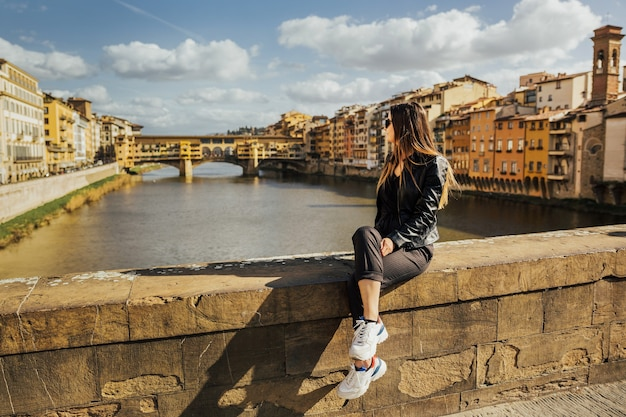 スタイリッシュな若い女性は、イタリア、フィレンツェのアルノ川と有名なヴェッキオ橋の背景に座っています