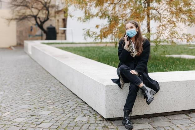 市内中心部に座って、会話のために現代の携帯電話を使用しているスタイリッシュな若い女性。パンデミックの時期に医療用保護マスクを着用した黒髪の女性。