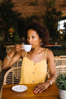 Stylish young woman sitting in the cafe drinking coffee