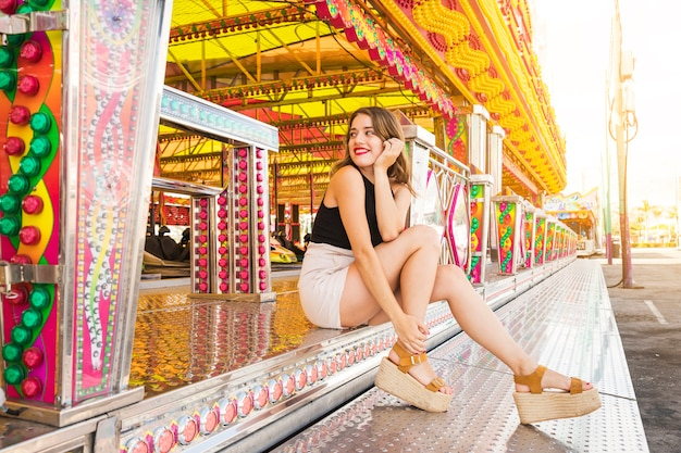 Stylish young woman sitting near the fairground ride