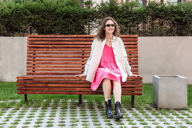 벤치에 앉아 웃고 있는 세련된 젊은 여성이 새로운 옷 컬렉션을 입고 포즈를 취하고 있다