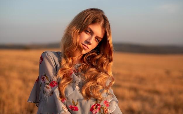 Стильная молодая женщина, стоящая в поле