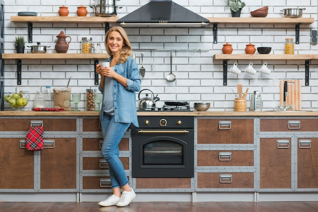 Stylish young woman standing in modular kitchen holding cup of coffee in hand