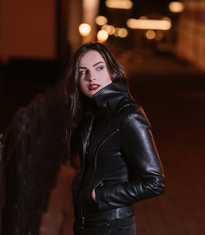 Stylish young woman standing in the night city.