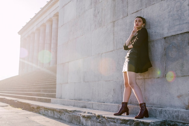 Stylish young woman standing in wall with sunlight