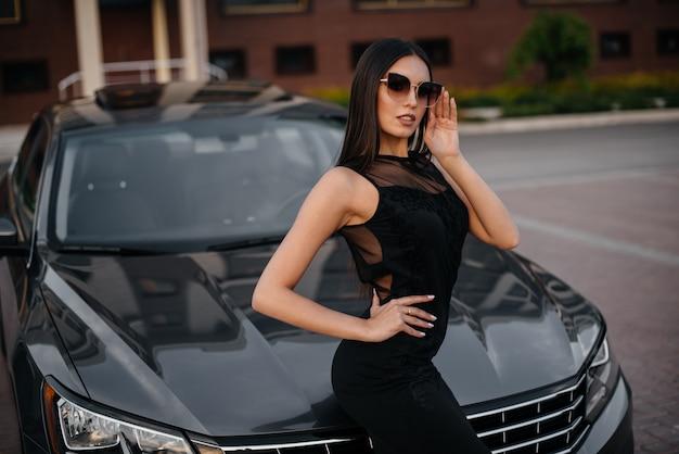 Стильная молодая женщина стоит возле машины в черном платье. деловая мода и стиль