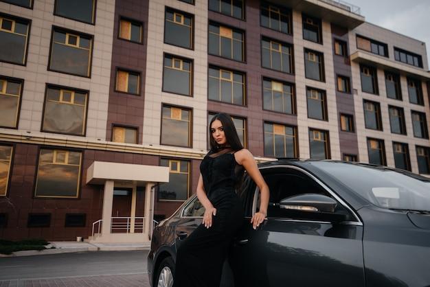 Стильная молодая женщина стоит возле машины в черном платье. деловая мода и стиль Premium Фотографии