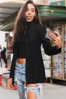 Stylish young woman sticking her tongue out while taking selfie on mobile phone