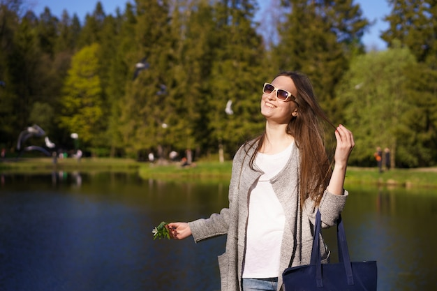 A stylish young woman in sunglasses with a bag and a flower in her hands walks against the background of a lake on a sunny day