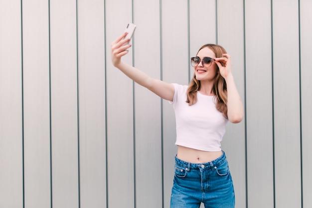 Stylish young woman take selfie posing on white wall