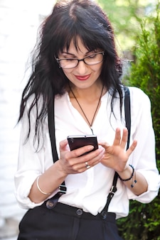 Stylish young woman uses a mobile phone. A female communicates with a smartphone, writes a