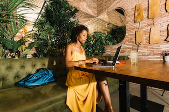 Stylish young woman using laptop sitting at the restaurant table with cocktail