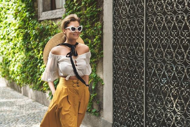 イタリアの小さな町の通りを歩くスタイリッシュな若い女性