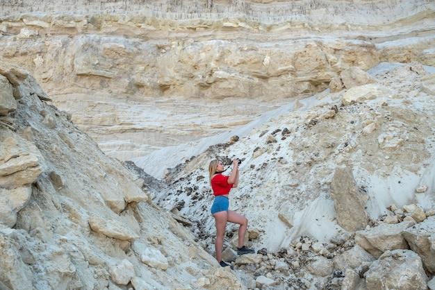 暑い夏の日、休暇で砂岩の中を歩くスタイリッシュな若い女性