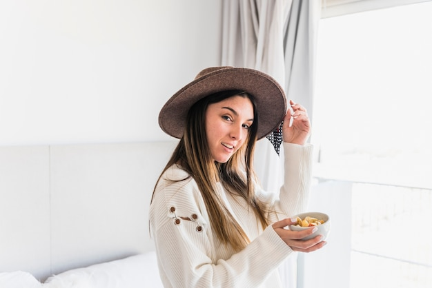 Stylish young woman wearing hat holding bowl of fruit salad