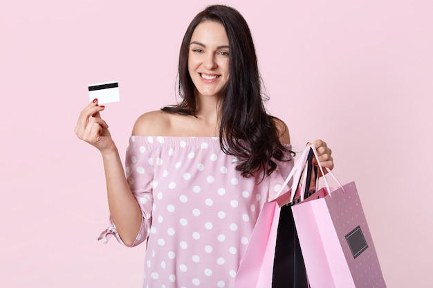 Стильная молодая женщина в платье в горошек, с сумками для покупок и кредитной карточкой, стоит с улыбкой на розовом, имеет приятное выражение лица, выражает радость и радость.