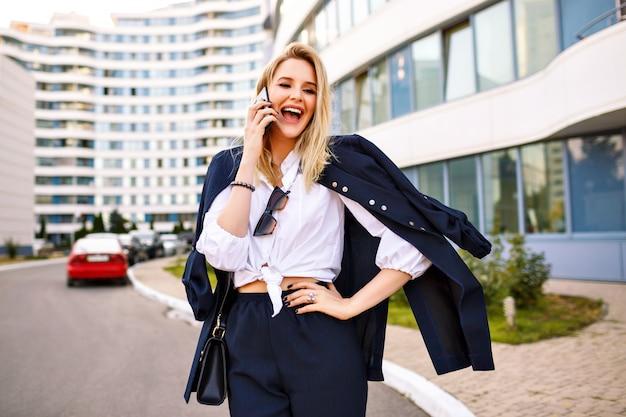 Стильная молодая женщина в модном темно-синем костюме, позирует возле современных зданий, модных аксессуаров, разговаривая по телефону, вызвала эмоции.