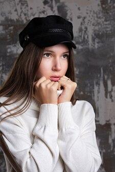 スタイリッシュな若い女性は、スタジオでポーズをとってキャップと白いニットのセーターを着ています