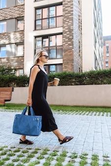 가방을 든 세련된 젊은 여성이 커피와 함께 도시 거리의 배경을 걷는다