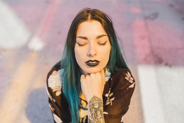 Stylish young woman with black lip and dyed hair closing her eyes