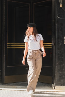 Stylish young woman with cap over her head walking on street
