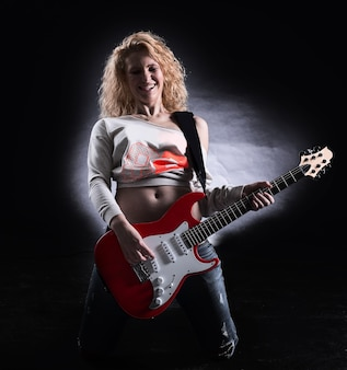 Stylish young woman with a guitar performing a rock song. isolated on a dark