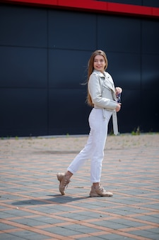 Stylish young woman with long blond hair of european appearance with a smile on her face. girl in a white jacket and white jeans a warm summer sunny day on a background of a gray building