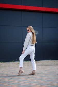 彼女の顔に笑顔でヨーロッパの外観の長いブロンドの髪を持つスタイリッシュな若い女性。灰色の建物の背景に白いジャケットと白いジーンズの暖かい夏の晴れた日の女の子