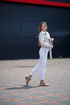 Стильная молодая женщина с длинными светлыми волосами европейской внешности с улыбкой на лице. девушка в белой куртке и белых джинсах в теплый летний солнечный день на фоне серого здания