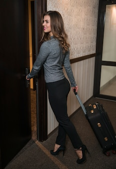 Stylish young woman with luggage bag opening the door in the hotel