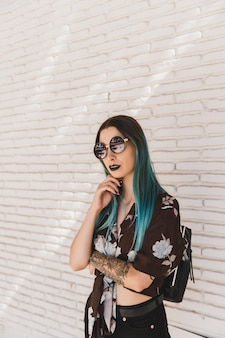Stylish young woman with sunglasses posing in front of wall