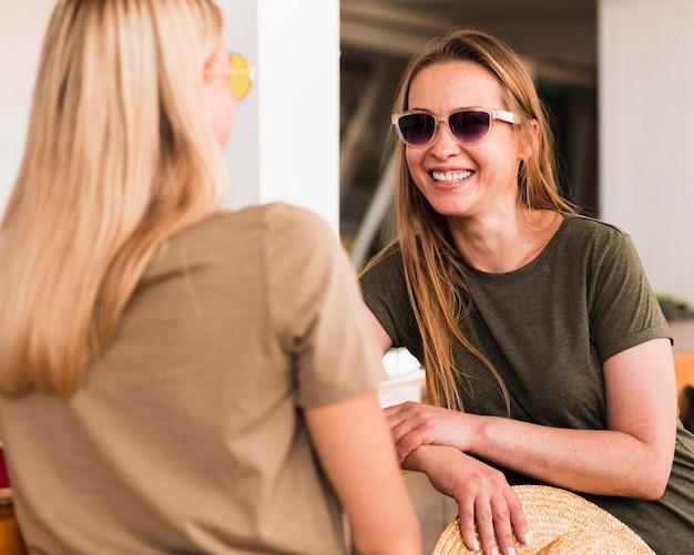 Стильные молодые женщины рады видеть друг друга