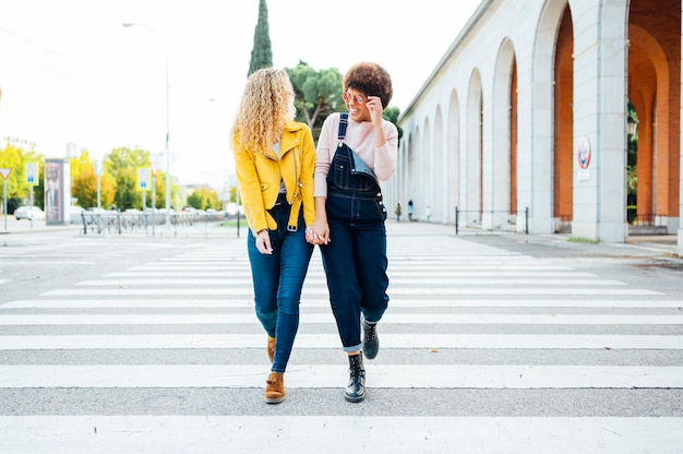 Stylish young women having friendly meeting walking in the street. lgtb concept