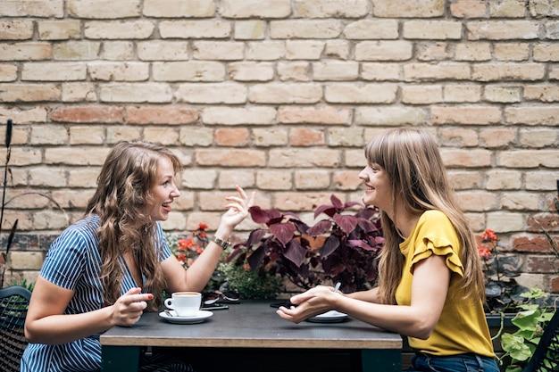 Стильные молодые женщины проводят дружескую встречу с чашками кофе, сидя за столом и болтая