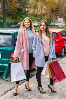 Stylish young women holding many colorful shopping bags posing on street