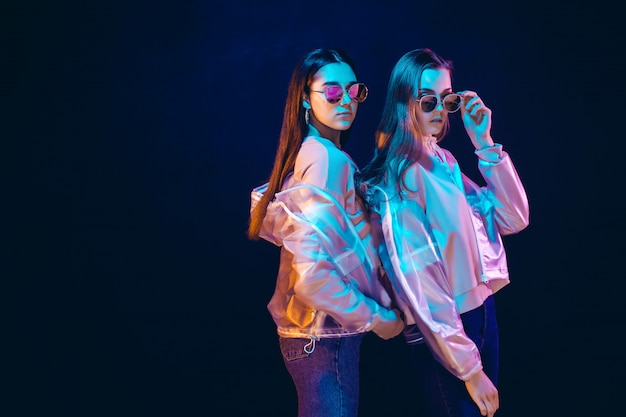 Stylish young women posing in neon light
