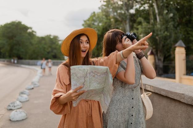봄의 트렌디한 드레스와 액세서리를 입고 함께 여행하는 세련된 젊은 여성들이 지도를 들고 카메라에서 사진을 찍는 것을 즐겁게 하고 있습니다.