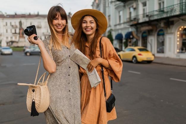 春の流行のドレスやアクセサリーを身に着けて一緒に旅行するスタイリッシュな若い女性は、地図を保持しているカメラで写真を撮ることを楽しんでいます