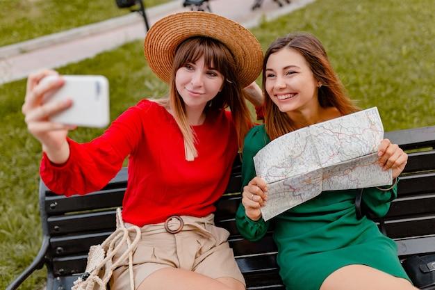 春の流行のドレスやアクセサリーを身に着けて一緒に旅行するスタイリッシュな若い女性は、地図を保持している電話のカメラで写真を撮ることを楽しんでいます