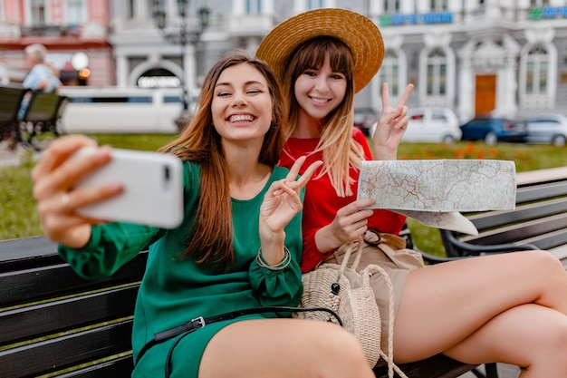 봄 유행의 드레스와 액세서리를 입고 함께 여행하는 세련된 젊은 여성들은 지도를 들고 전화 카메라로 사진을 찍는 재미를 즐깁니다.
