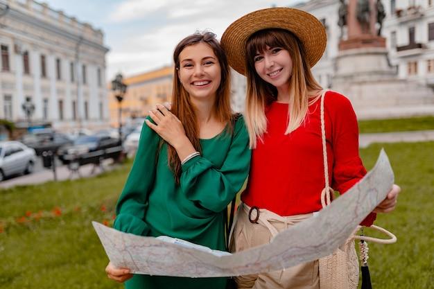 春の流行の服やアクセサリーを身に着けて一緒に旅行するスタイリッシュな若い女性は、地図を持って楽しんでいます