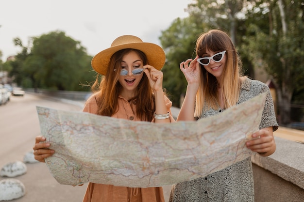 Stylish young women traveling together dressed in spring trendy dresses and accessories having fun taking photo on camera holding map