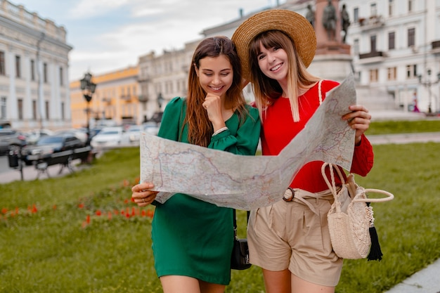 Stylish young women traveling together dressed in spring trendy outfit and accessories having fun holding map