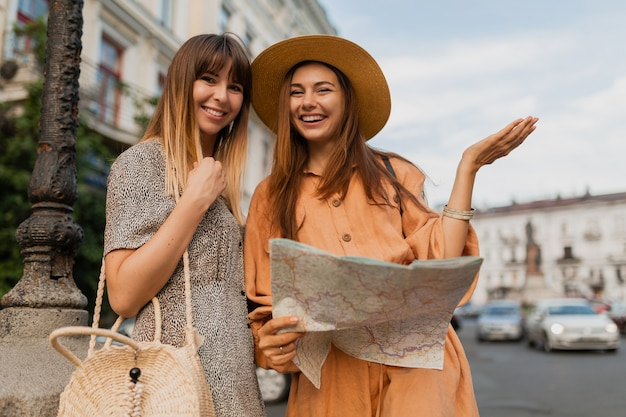 Stylish young women traveling together in europe dressed in spring trendy dresses and accessories