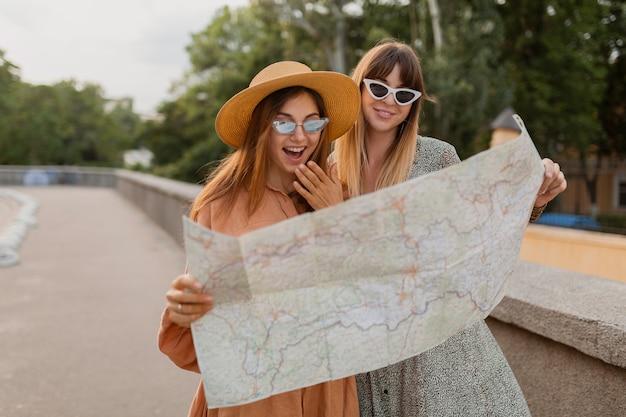 봄의 트렌디한 드레스와 액세서리를 입고 유럽을 함께 여행하는 세련된 젊은 여성